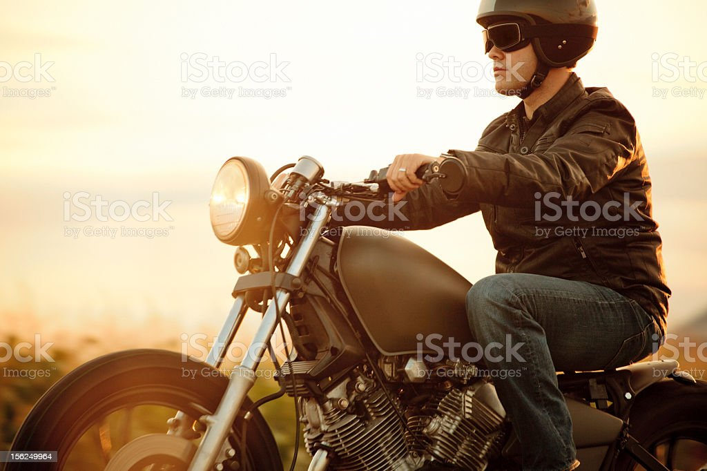 A man riding a motorcycle in the sunset stock photo