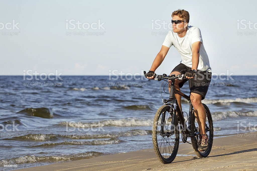 Man riding bicycle in beach stock photo