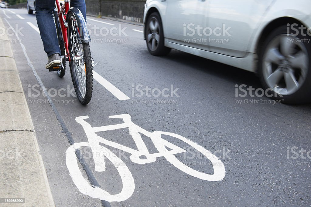 Man riding bicycle in cycle lane stock photo