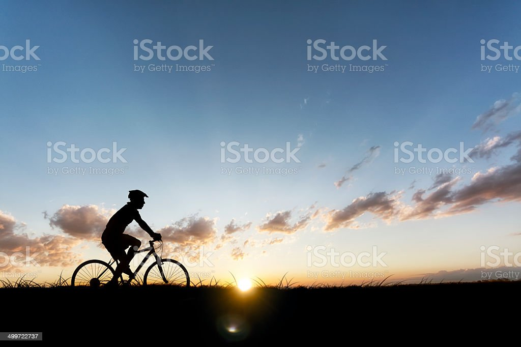 Man Riding Bike at Sunset in the Country royalty-free stock photo