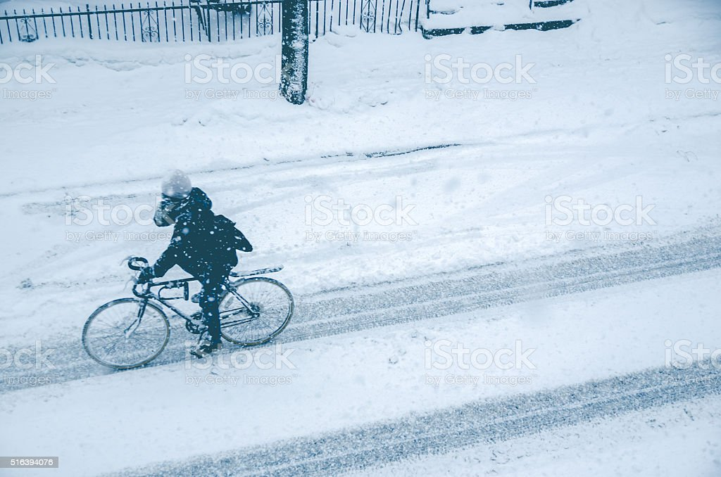 Man riding bike during snow storm stock photo
