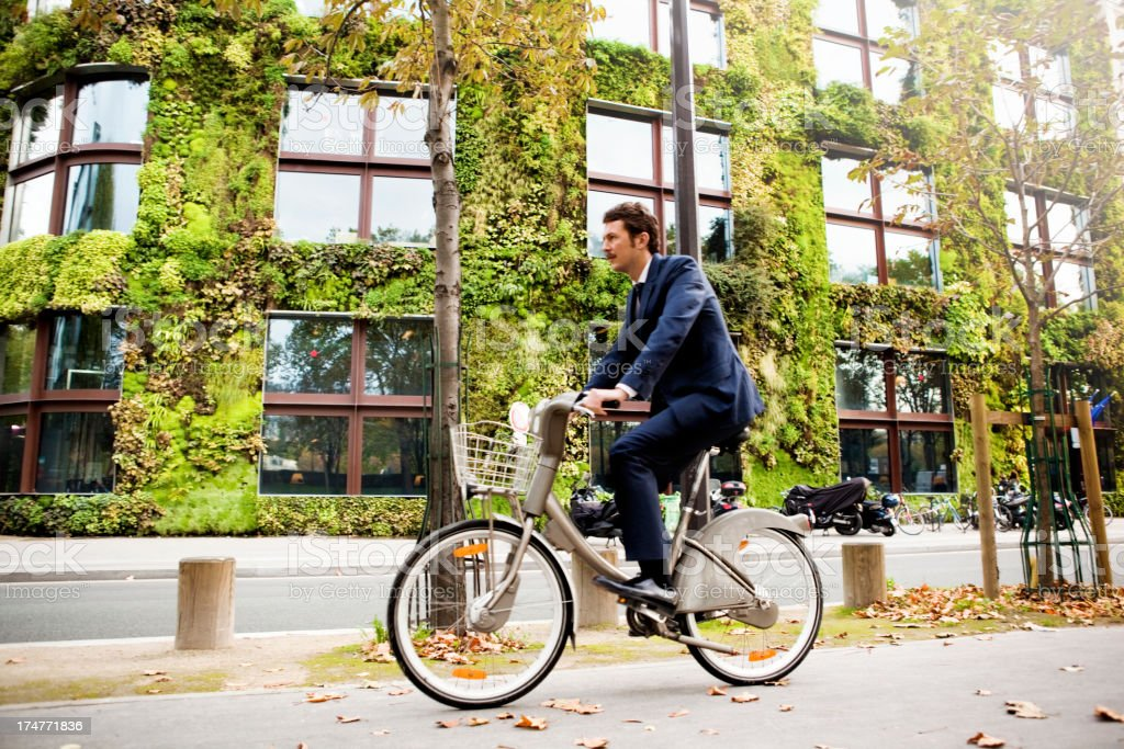 Man riding bike in front of vertical garden stock photo