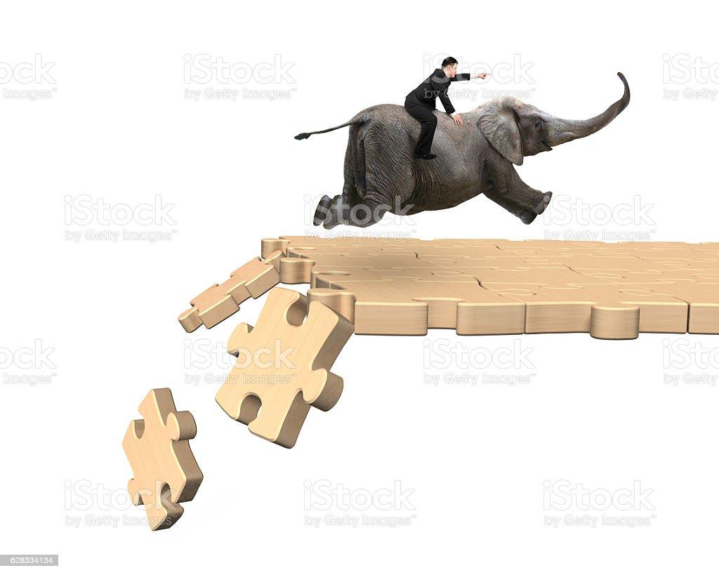 Man riding elephant on breaking puzzle path stock photo