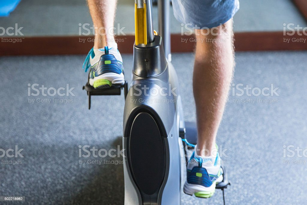 Man riding indoor bicycle stock photo