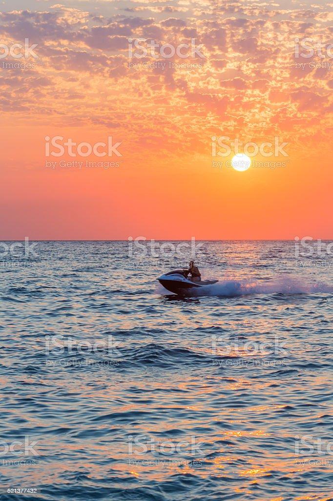 Man riding jet ski on colorful sunset stock photo