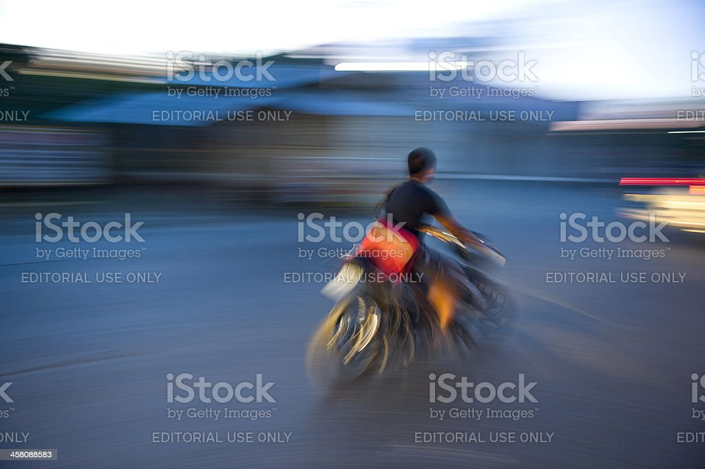 Man riding motorcycle in street at sunset moment royalty-free stock photo