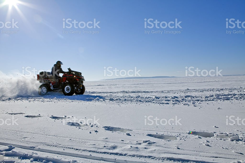 man riding quad bike on snowy winter field stock photo