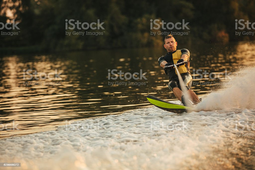 Man riding wakeboard on wave of motorboat stock photo