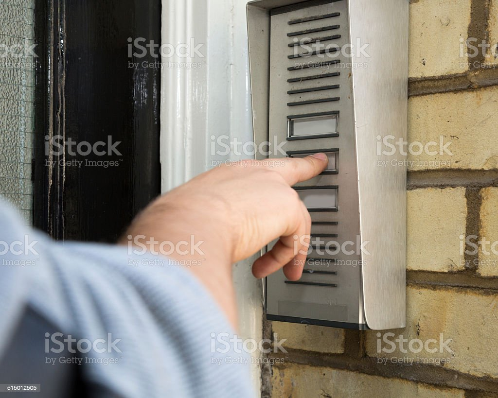 Man ringing an intercom to gain access stock photo