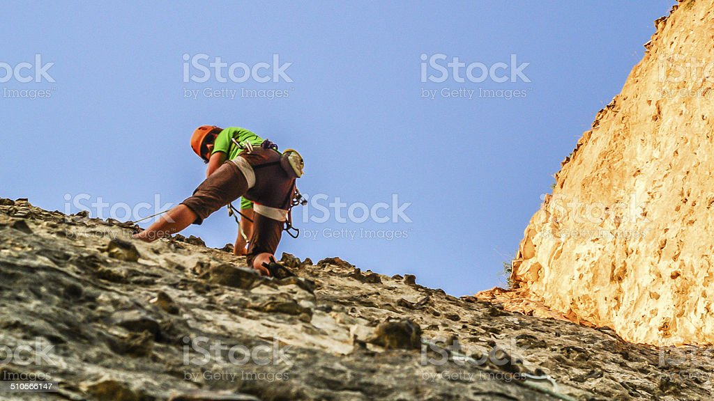Man rock climber clinging to a cliff stock photo