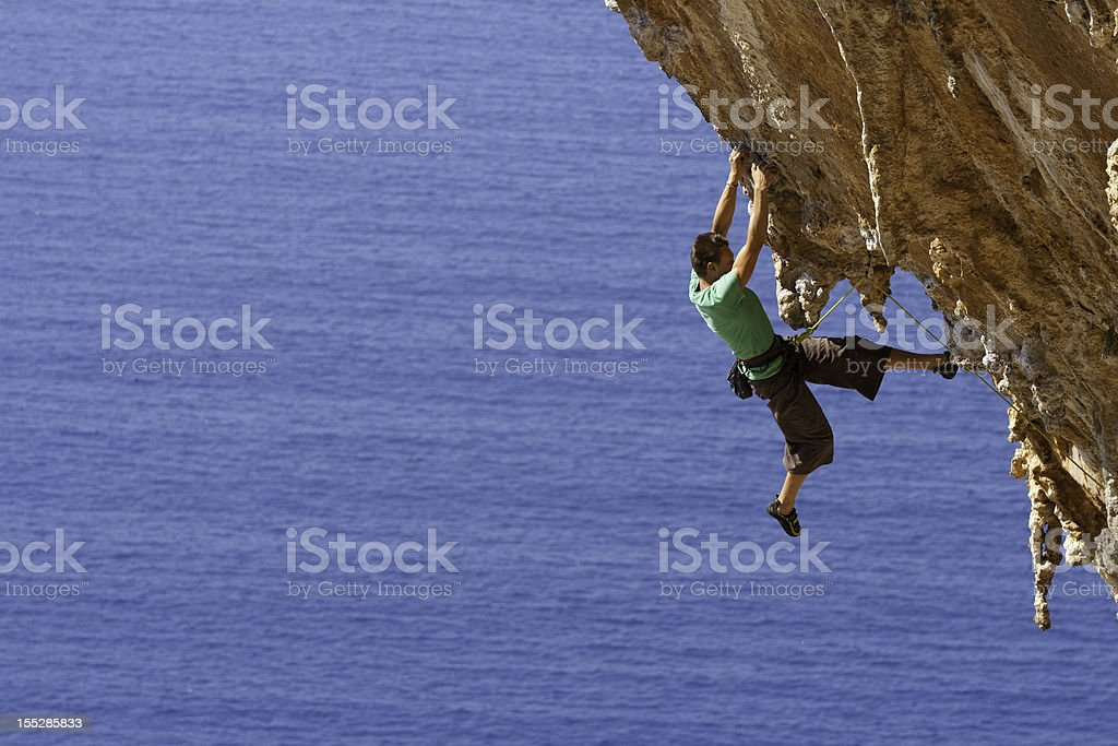 A man rock climbing on a large steep cliff near the ocean royalty-free stock photo