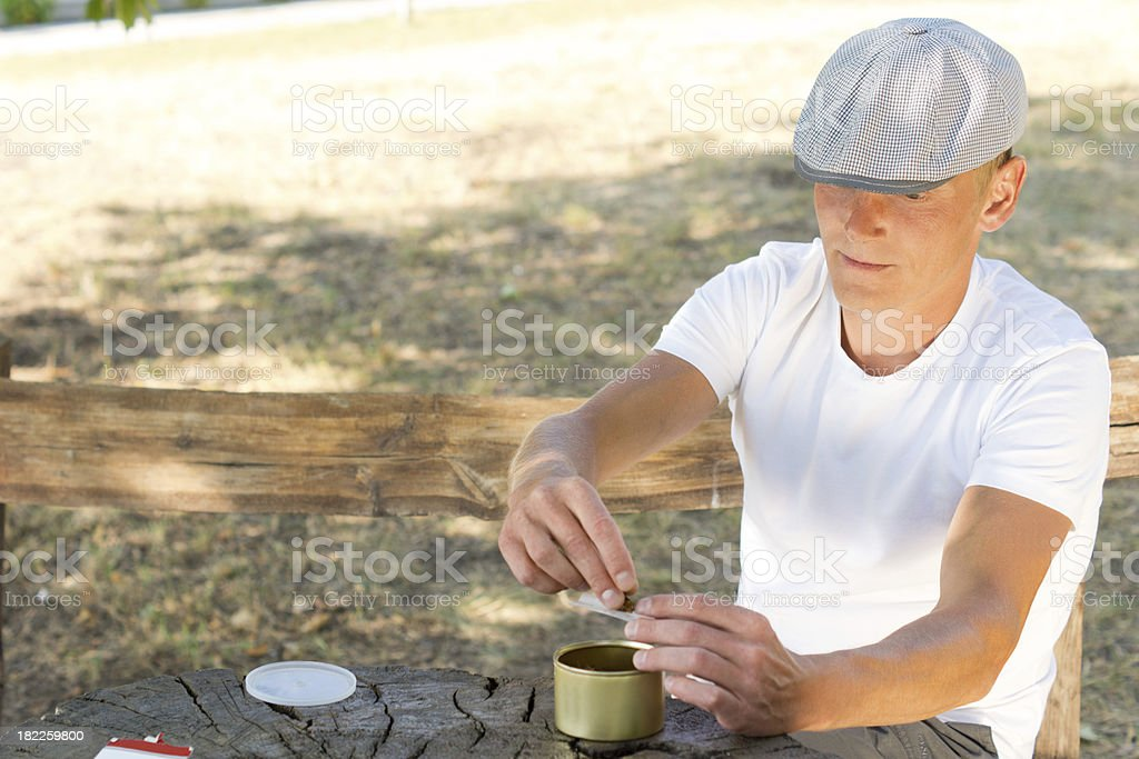 Man rolling himself a cigarette royalty-free stock photo