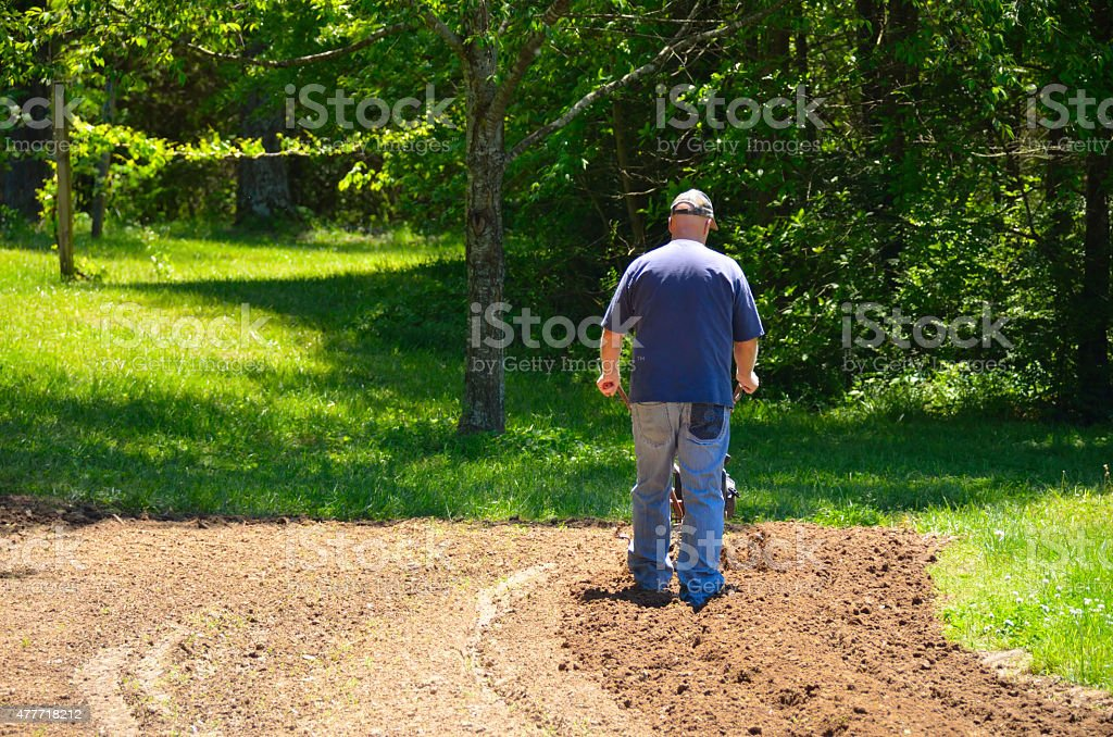Man rototilling garden stock photo