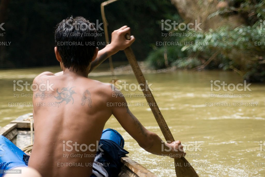 Man rowing a boat on Sarawak River stock photo