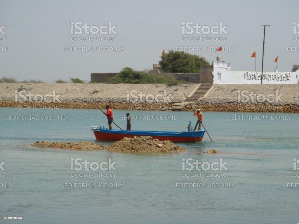 Man rowing boat on the Gomti River in Dwaraka,India stock photo