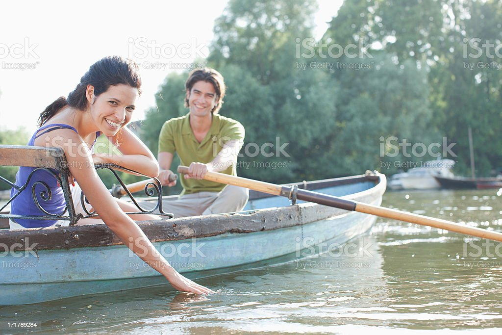 Man rowing girlfriend in rowboat on lake stock photo