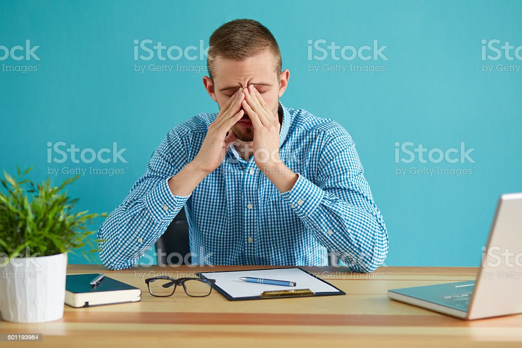 Man rubbing his eyes stock photo