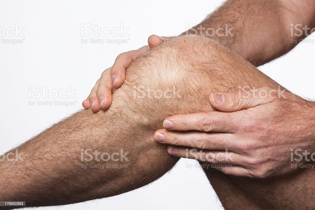 A man rubbing his knee because his knee is in pain stock photo