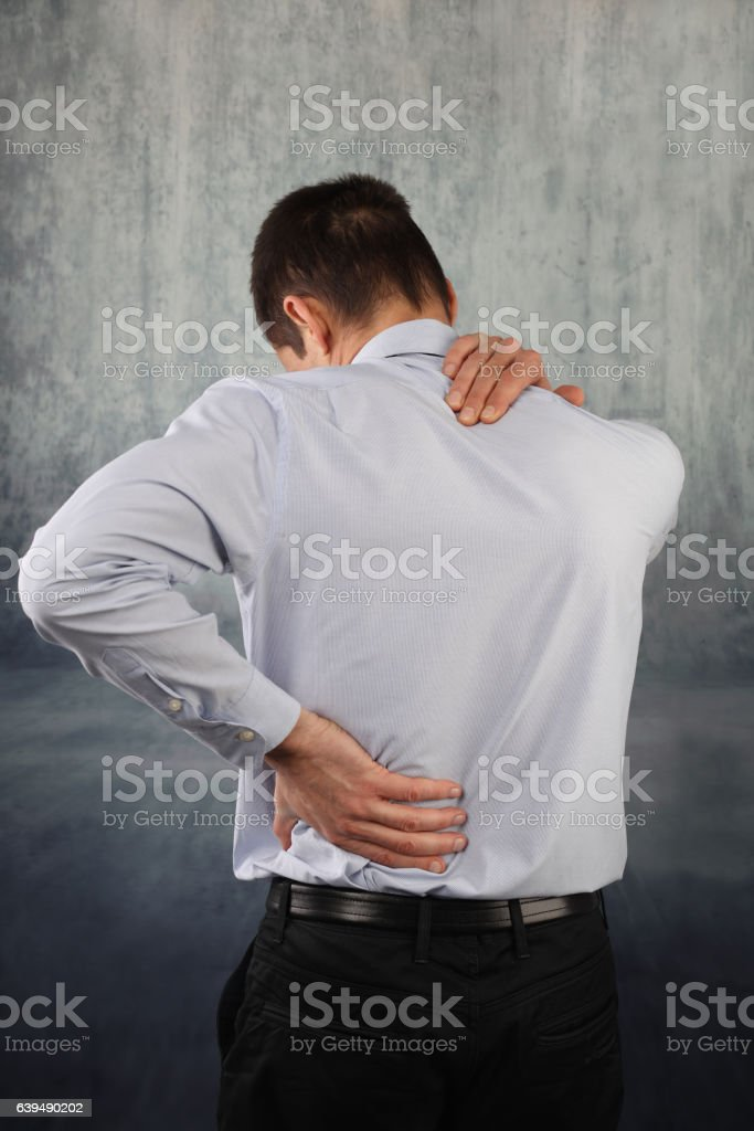 Man rubbing his painful back and neck close up. stock photo