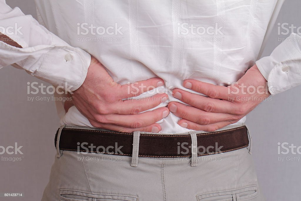 Man rubbing his painful back stock photo
