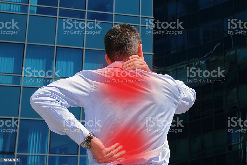 Man rubbing his painful neck. Business man with back pain. stock photo