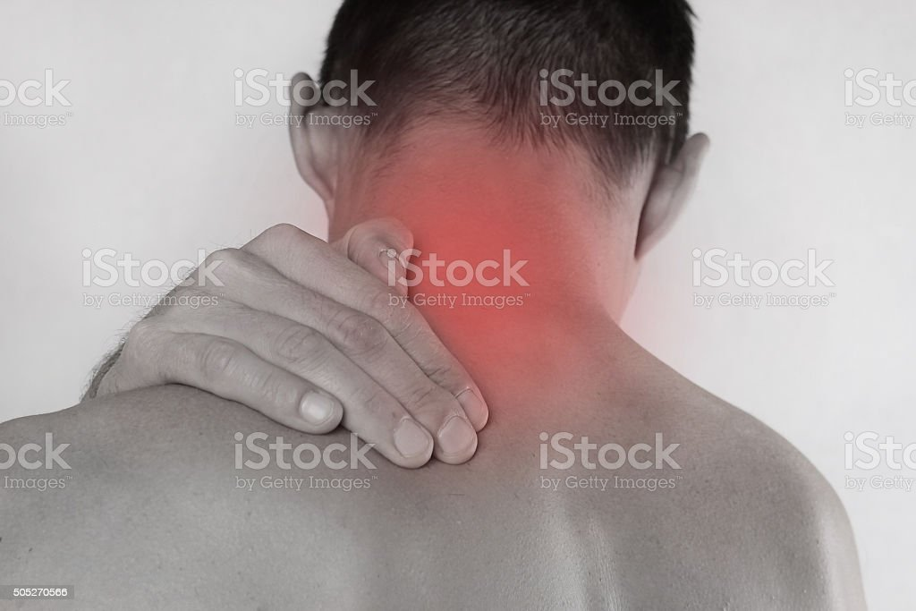 Man rubbing his painful neck. Pain relief concept stock photo