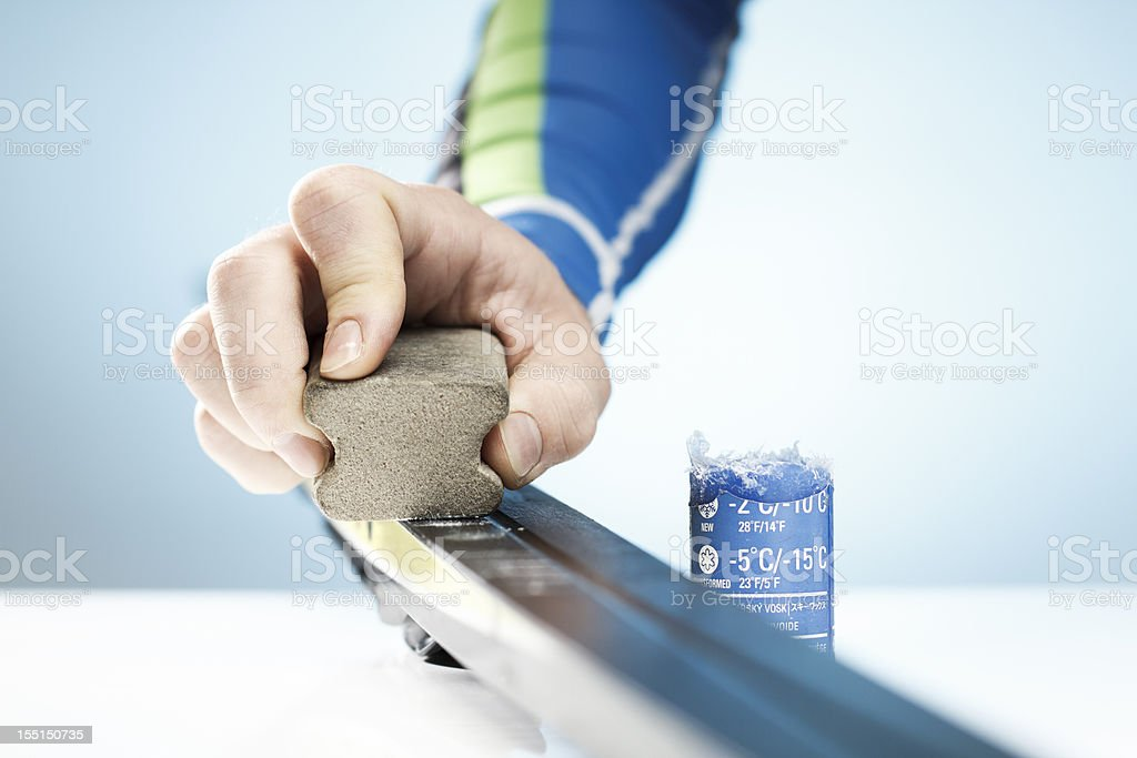 A man rubbing wax on his cross country skis stock photo