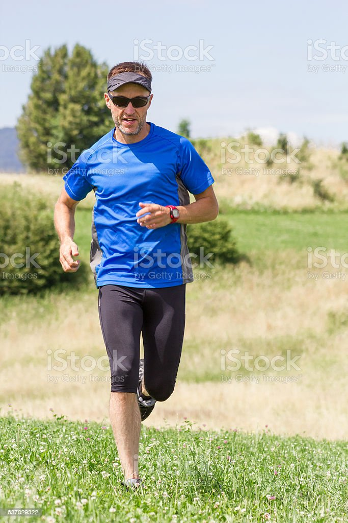 Man runner training in mountains stock photo