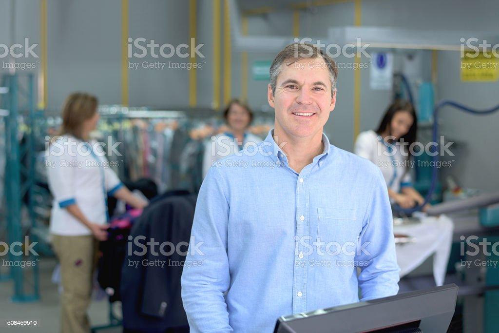 Man running a laundry service shop stock photo