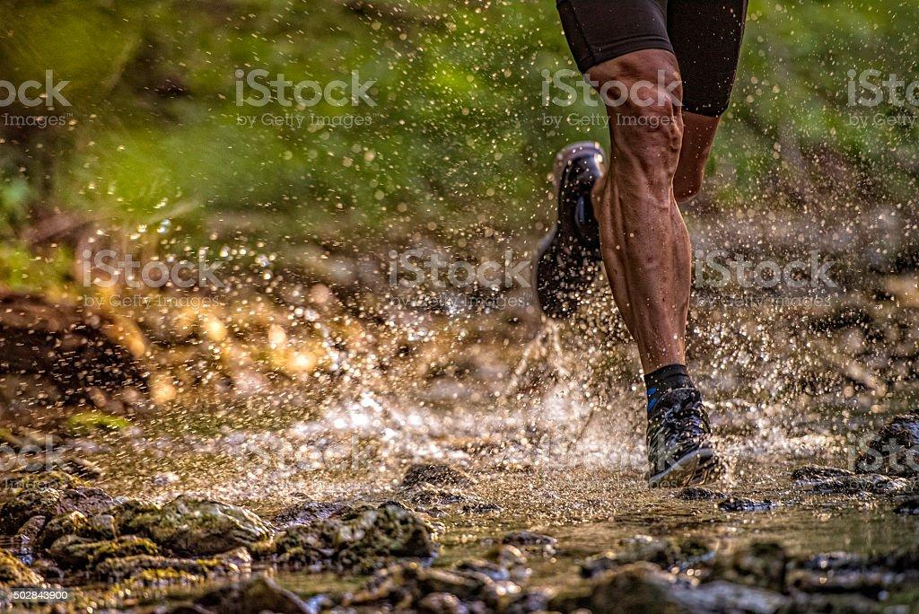 Man running across a stream, water splashing stock photo