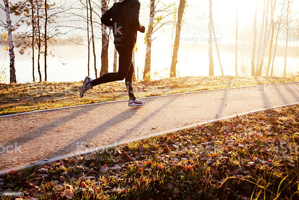 Man running at autumn during sunrise stock photo