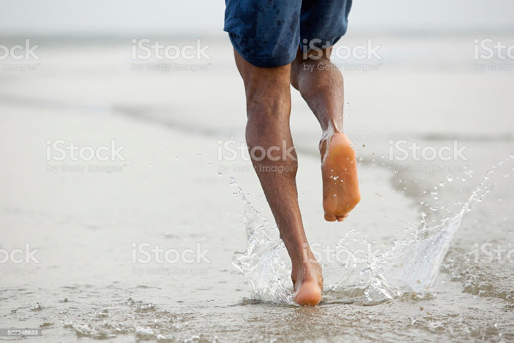 Man running barefoot in water stock photo
