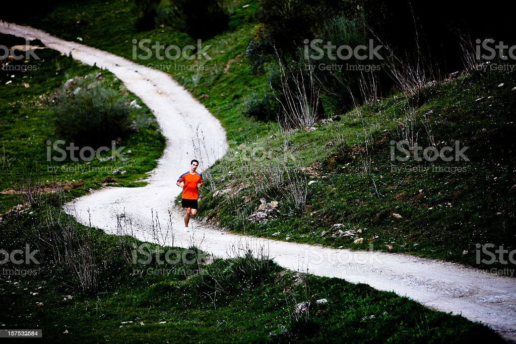 Man running down a winding road royalty-free stock photo