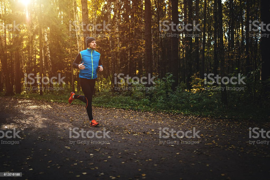 Man running in forest on sunrise stock photo