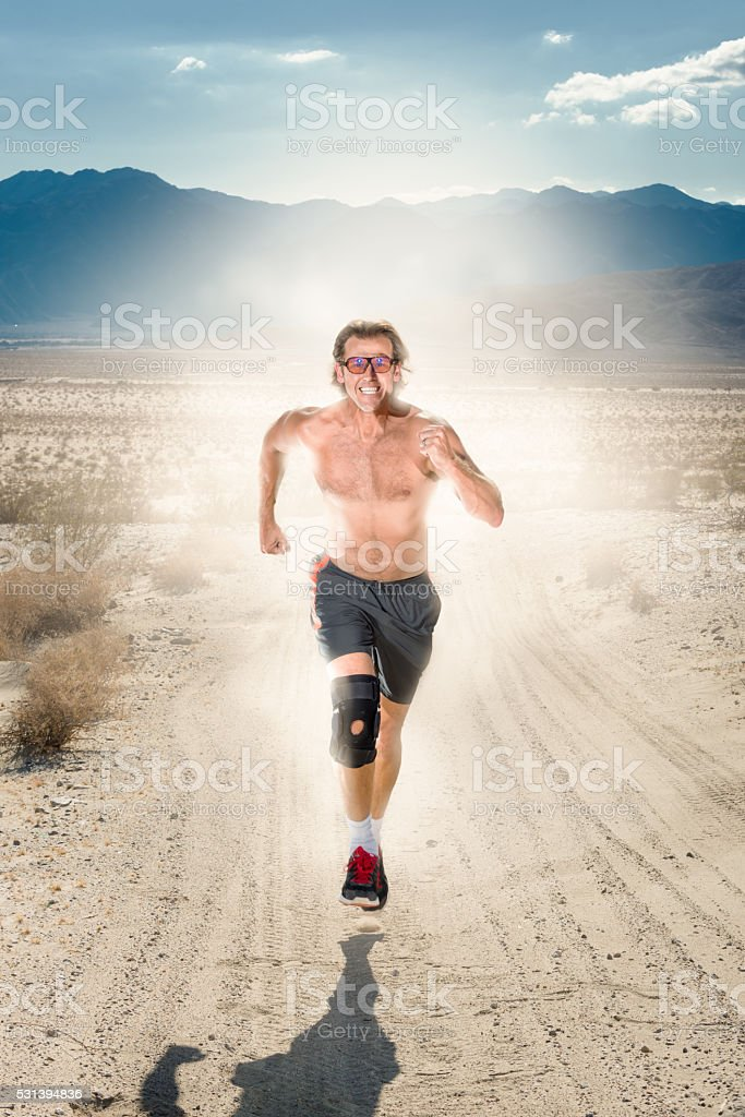 Man Running In The Desert With A Trail Of Dust stock photo