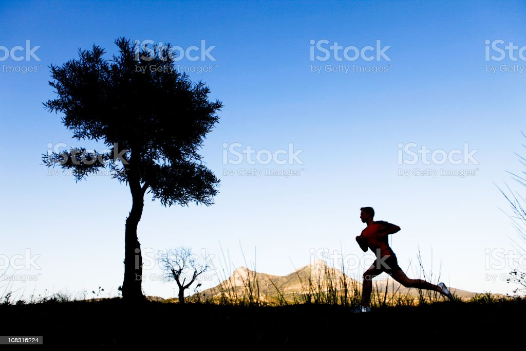 Man running on a trail at sunset royalty-free stock photo