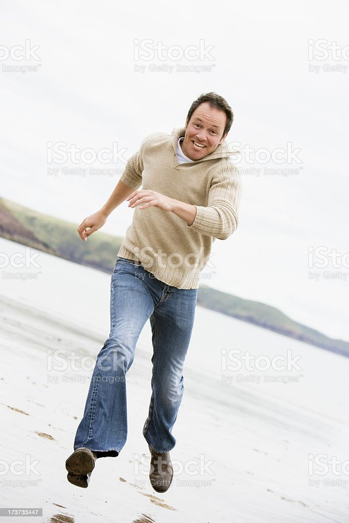 Man running on beach smiling royalty-free stock photo