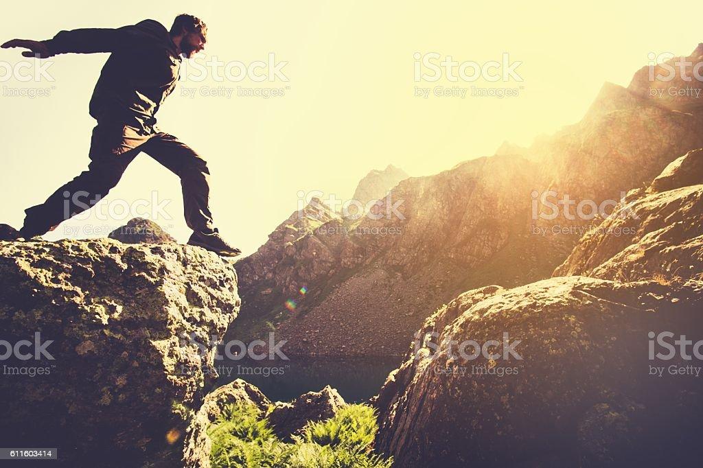 Man running on Mountains jumping cliff over lake Skyrunning sport stock photo