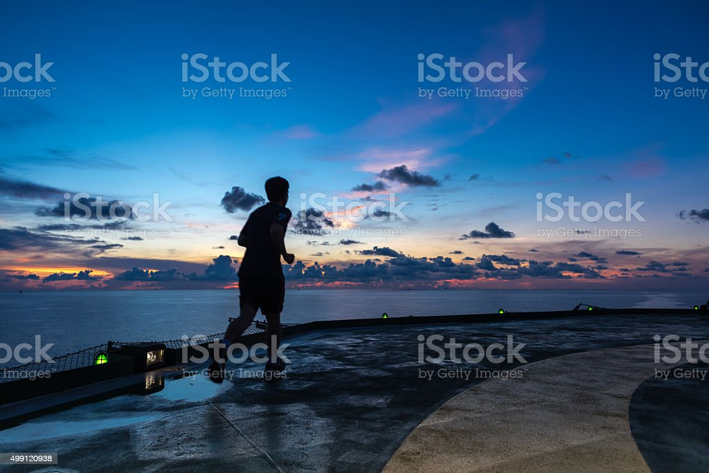 Man running on oil rig helipad in sunset time stock photo