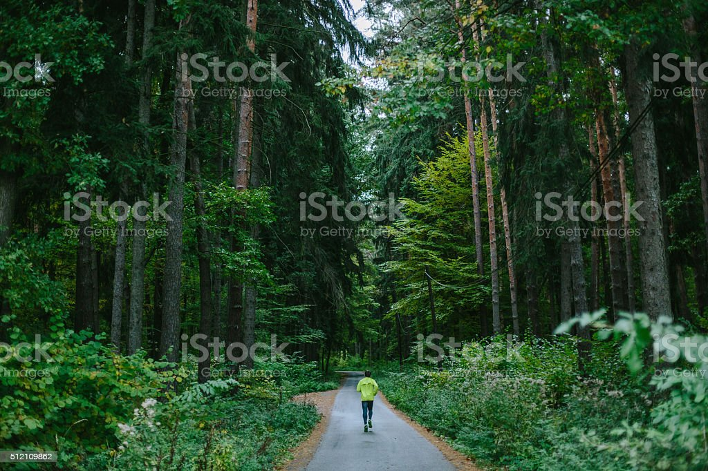 Man running on path in old green forest. stock photo