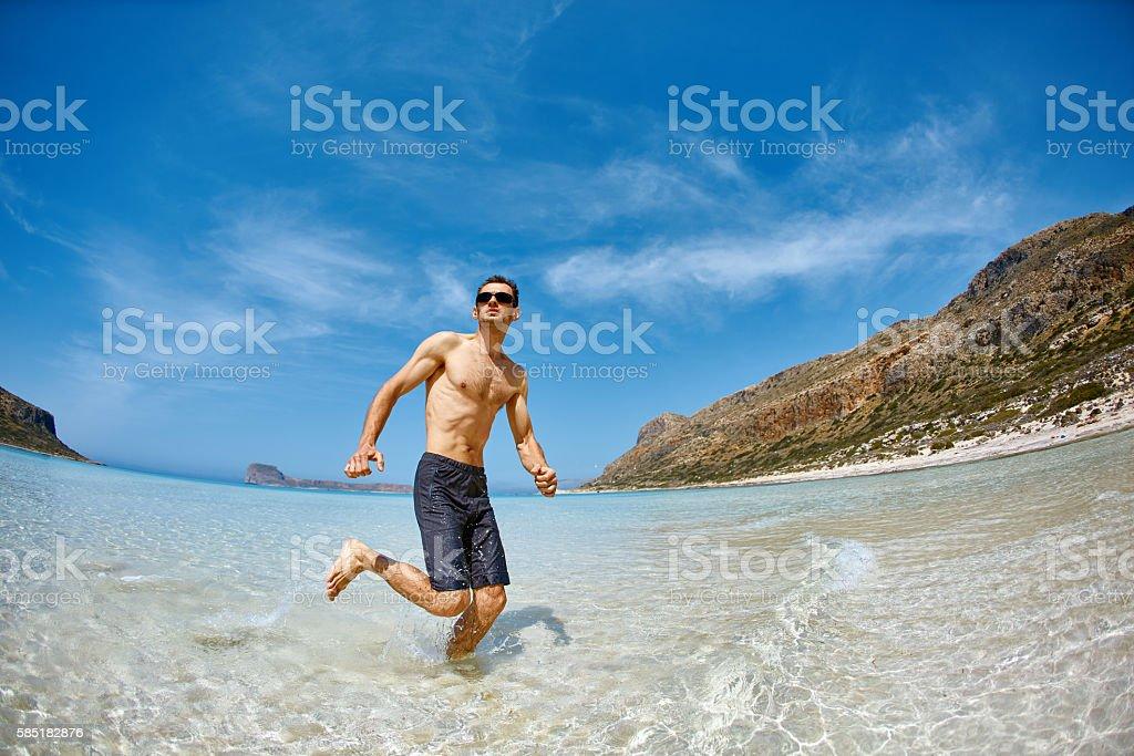 man running on the beach stock photo