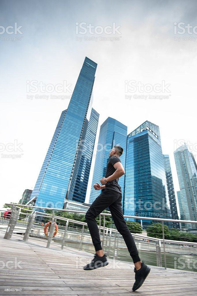 man running on the city of singapore marina bay area stock photo