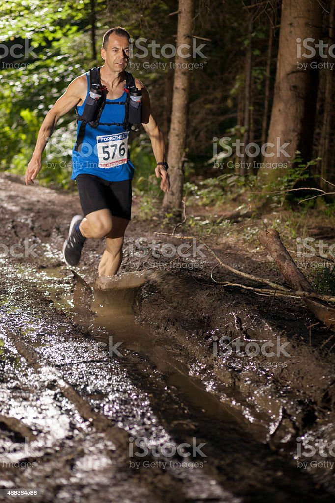 Man running through dirt track in ultramarathon race stock photo