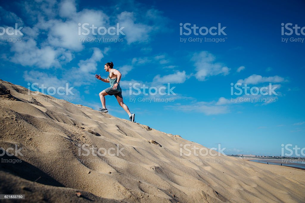 Man Running Up A Sand Dune stock photo