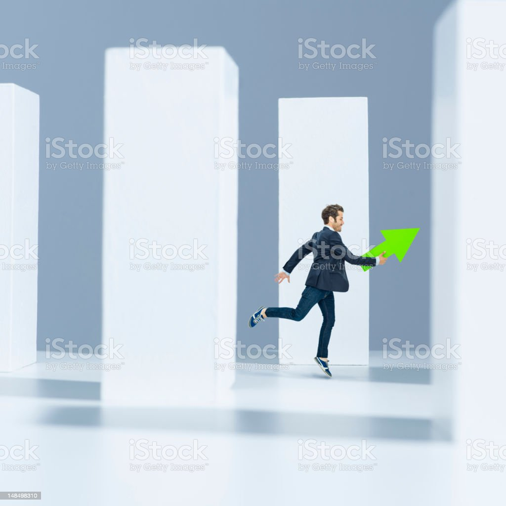 Man running with green arrow in modern space royalty-free stock photo