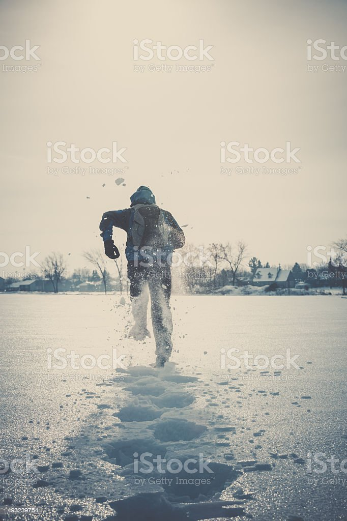Man Running with Snowshoes in Winter stock photo