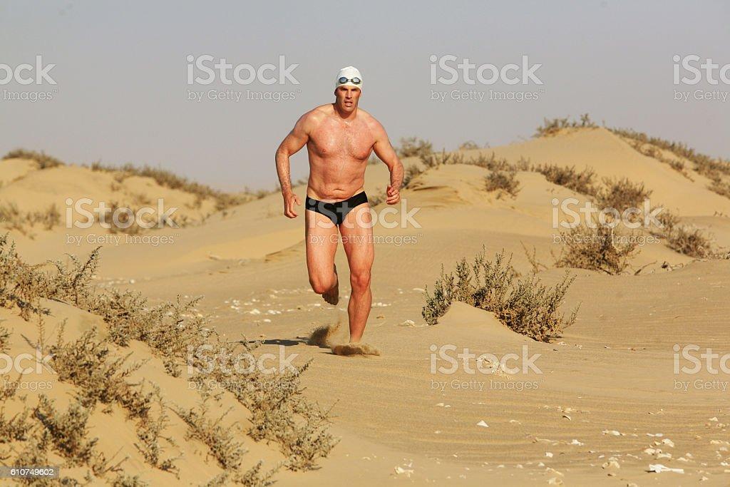Man runs along dune with scrubby plants stock photo