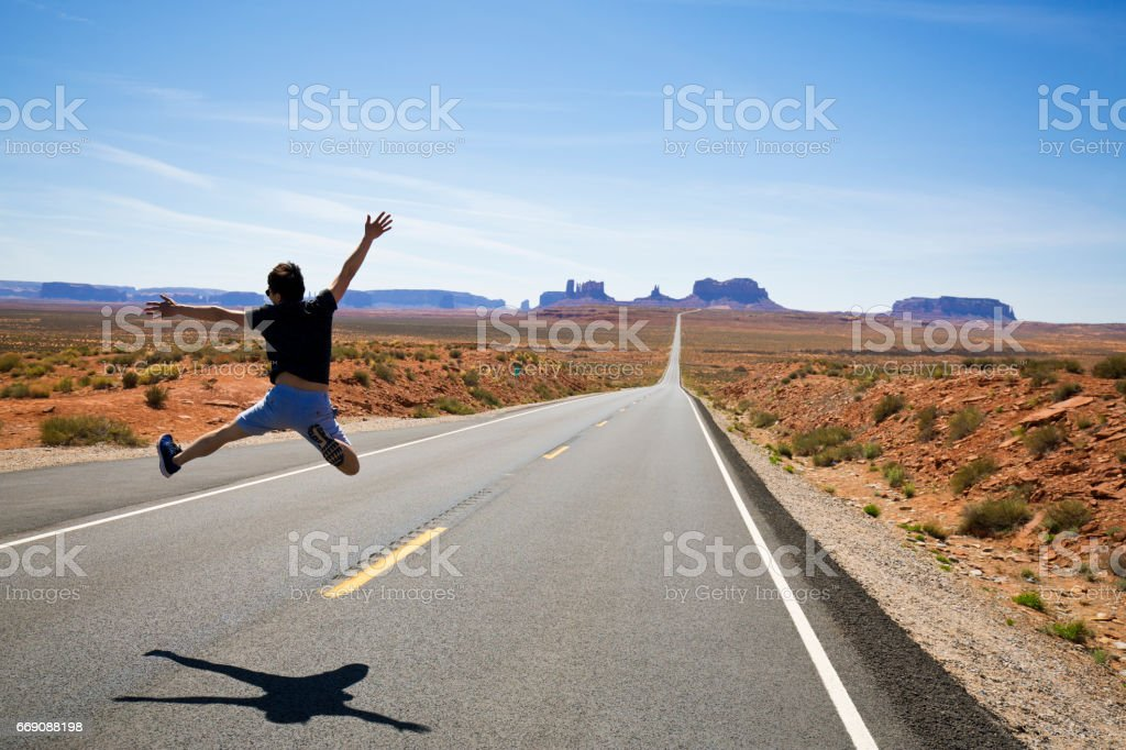 A man runs and jumps along a section of Highway 163 in Monument Valley, Utah, USA. stock photo