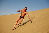 Man runs down a dune
