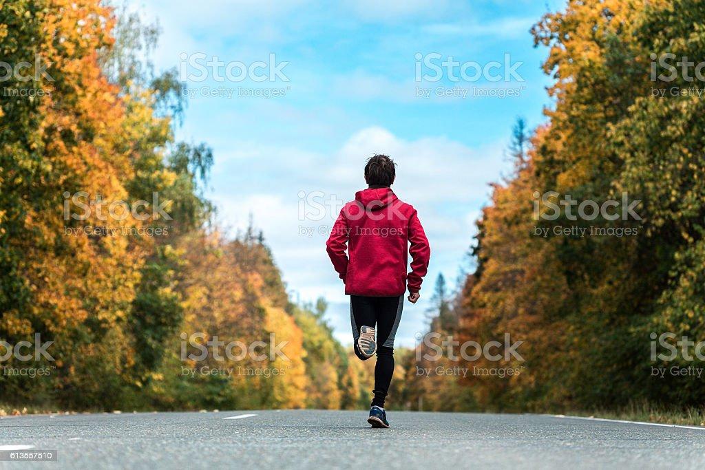 Man runs on the road stock photo
